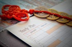 Feche acima de uma parte de um caderno e de umas moedas chinesas em um laço vermelho fotos de stock royalty free