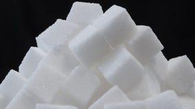 Feche acima de uma pilha de cubos do açúcar contra um fundo preto vídeos de arquivo