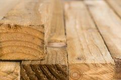 Feche acima de uma pilha de sarrafos de madeira com um fundo borrado f Imagem de Stock Royalty Free