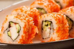 Feche acima de Uramaki Califórnia Rolos de sushi com nori, arroz, partes Fotografia de Stock