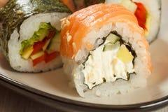 Feche acima de Uramaki Philadelphfia Rolos de sushi com salmões, nori, ri Fotografia de Stock Royalty Free