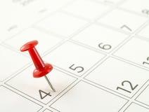 Feche acima do único pino vermelho do impulso tacheado em 4o julho na página do calendário de mesa Fotografia de Stock