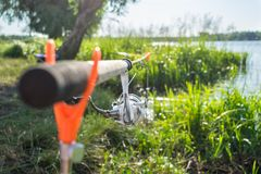 Feche acima do alimentador e do carretel da vara de pesca montados nos suportes em t imagem de stock