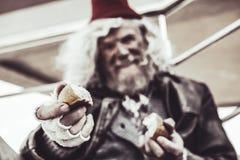 Feche acima do almsman idoso cujo guardando partes de cozimento e compartilhando d com o fotógrafo foto de stock royalty free