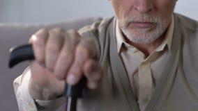 Feche acima do ancião com bastão, inabilidade de passeio e problemas comum, saúde filme