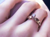 Feche acima do anel de diamante elegante no dedo com fundo cinzento do lenço Diamond Ring foto de stock