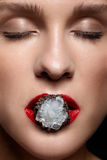 Feche acima do anel do bijouterie com a pedra nos bordos fêmeas vermelhos da boca Imagem de Stock Royalty Free