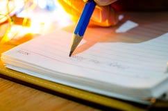 Feche acima do ano novo feliz da escrita masculina na nota de papel Foto de Stock Royalty Free