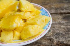 Feche acima do aroma delicioso suculento do abacaxi, corte em partes no prato na tabela como o fundo fotos de stock