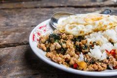 Feche acima do arroz coberto com carne de porco salteado e manjericão com o ovo frito colocado em uma tabela pronta para ser serv imagem de stock royalty free