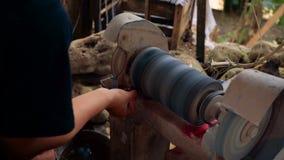 Feche acima do artesão de pedra preciosa que usa a máquina de moedura filme