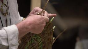 Feche acima do artesão que veste a roupa rural que faz a cesta de vime dos galhos Técnica de tecelagem feito a mão tradicional na video estoque
