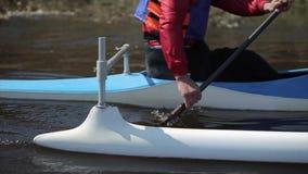 Feche acima do atleta deficiente que usa a pá em uma canoa Enfileiramento, canoeing, remando Treinamento kayaking esporte paraoly video estoque