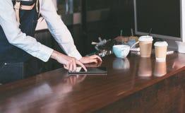 Feche acima do avental de brim do desgaste da empregada de mesa do barista usando a tabuleta na contagem Fotografia de Stock Royalty Free