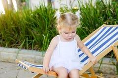 Feche acima do bebê blondy adorável na criança do vestido ou da criança que senta-se e que relaxa em um sunbed ou em um deckchair foto de stock
