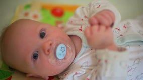 Feche acima do bebê bonito com o Soother que encontra-se na ucha video estoque