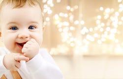 Feche acima do bebê doce sobre luzes de Natal fotografia de stock