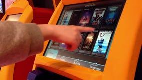 Feche acima do bilhete de compra do filme da mulher no cineplex video estoque