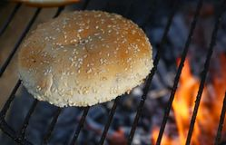 Feche acima do bolo do sésamo para o hamburguer na grade do fogo do BBQ Fotografia de Stock