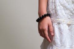 Feche acima do bracelete de pedra do grânulo na mão da menina Imagem de Stock