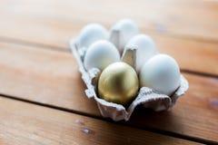 Feche acima do branco e dos ovos do ouro na caixa de ovo Imagem de Stock Royalty Free