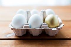 Feche acima do branco e dos ovos do ouro na caixa de ovo Foto de Stock Royalty Free