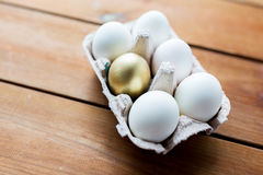 Feche acima do branco e dos ovos do ouro na caixa de ovo Fotos de Stock
