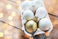 Feche acima do branco e dos ovos do ouro na caixa de ovo Foto de Stock