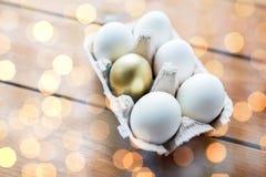 Feche acima do branco e dos ovos do ouro na caixa de ovo Fotografia de Stock