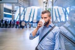 Feche acima do café bebendo do homem de negócios do moderno, estação de metro Imagens de Stock