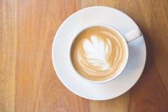 Feche acima do café da arte do latte na tabela com estilo do vintage Fotos de Stock Royalty Free