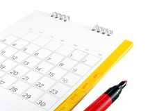 Feche acima do calendário de mesa branco do cartão com dias e data e da pena de marcador vermelha isolada no fundo branco foto de stock royalty free