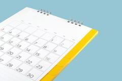 Feche acima do calendário de mesa do cartão com os dias e a data isolados no fundo azul imagem de stock royalty free