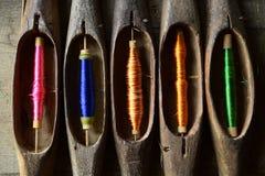 Feche acima do carretel com a linha colorida no equipamento local de madeira fotografia de stock royalty free