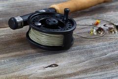 Feche acima do carretel e das moscas da mosca na madeira Fotos de Stock
