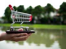 Feche acima do carrinho de compras no telefone celular, negócio no conceito do comércio eletrónico Fotografia de Stock
