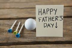 Feche acima do cartão com texto feliz do dia de pais pela bola de golfe e pelos T imagem de stock