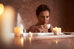 Feche acima do chá da bebida da jovem senhora no banho relaxado fotografia de stock