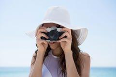 Feche acima do chapéu vestindo da mulher ao fotografar fotos de stock royalty free