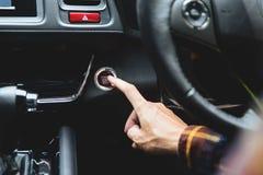 Feche acima do começo e da parada do motor de automóveis das funções do botão da imprensa do dedo foto de stock