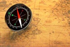 Feche acima do compasso magnético no mapa velho Foto de Stock Royalty Free