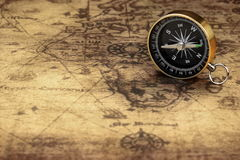 Feche acima do compasso magnético no mapa velho Foto de Stock