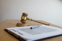 Feche acima do conceito da lei do objeto Julgue o martelo com os advogados e os originais de justiça que trabalham na tabela fotografia de stock