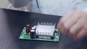 Feche acima do conjunto manual de componentes eletrônicos em uma placa video estoque