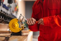 Feche acima do contramestre na roupa de trabalho alaranjada usando o apontador de faca dentro fotografia de stock