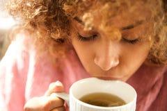 Feche acima do copo bebendo da mulher negra nova do chá fotos de stock
