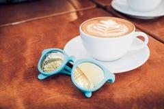 Feche acima do copo de café branco com arte e sungla do latte da forma do coração fotografia de stock royalty free