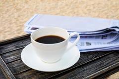 Feche acima do copo de café branco na tabela de madeira na praia da areia do nascer do sol com o jornal na manhã Fotos de Stock