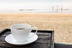 Feche acima do copo de café branco na tabela de madeira na praia da areia do nascer do sol na manhã fotos de stock royalty free