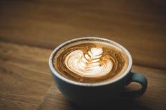 Feche acima do copo de café quente do cappuccino com arte do latte da forma do coração na tabela de madeira no filtro do café, do fotografia de stock